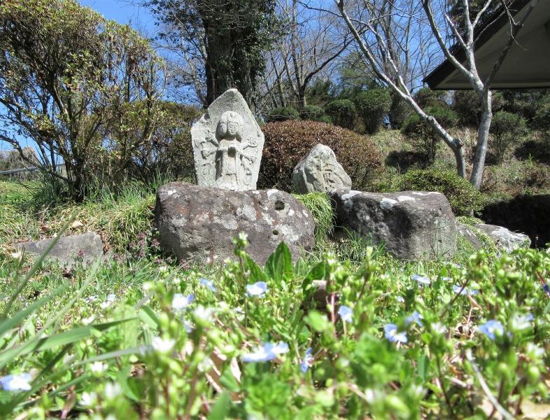 暖かな春の陽射しを浴びる、忠恩寺の千手観音像と三界萬霊塔